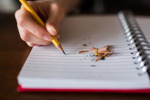 Writing in pencil on lined paper with pencil shavings